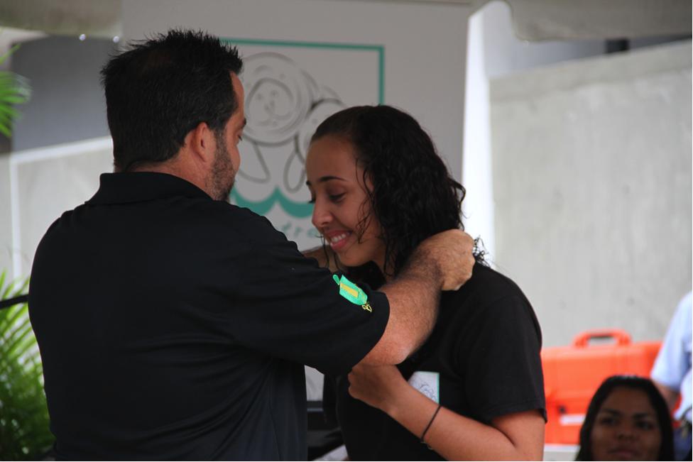 El doctor Antonio Mignucci, director del Centro de Conservación de Manatíes en el Recinto de Bayamón de la Universidad Interamericana, le obsequia un collar a Nicole Gutiérrez como un símbolo de agradecimientos a los estudiantes técnicos y voluntarios que cuidan diariamente a estos mamíferos.